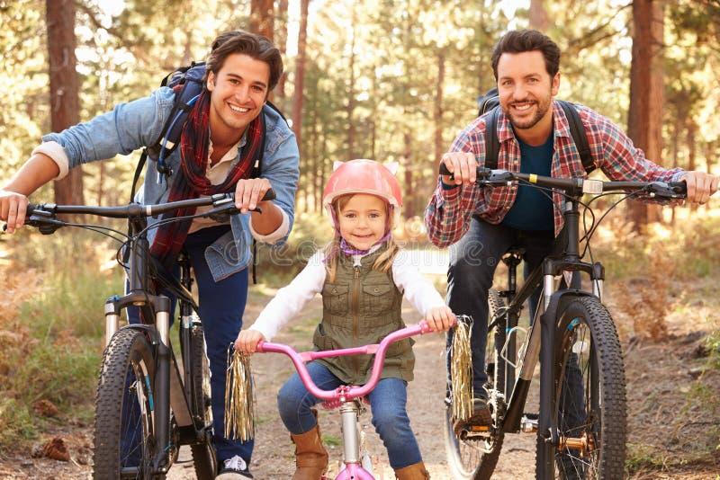 Glade manliga par med dottern som cyklar till och med nedgångskogsmark royaltyfria foton