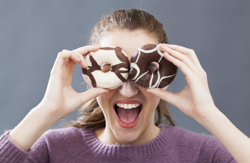 Glade nederlagögon för ung kvinna med donuts för roligt skämt royaltyfri foto