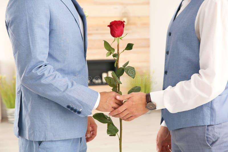 Glade par för lycklig nygift person med blomman hemma fotografering för bildbyråer