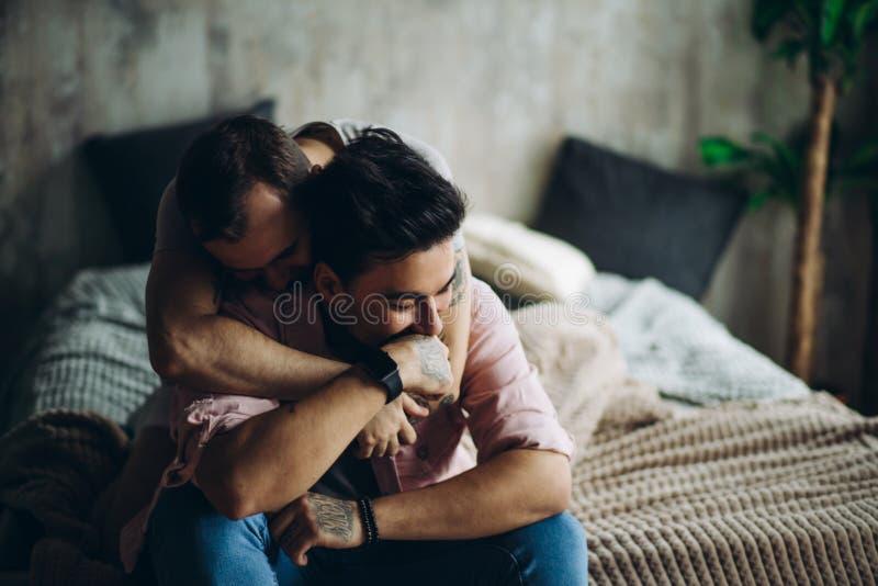 Glade par hemma, intima ögonblick av privat liv - homosexuella partners arkivfoto