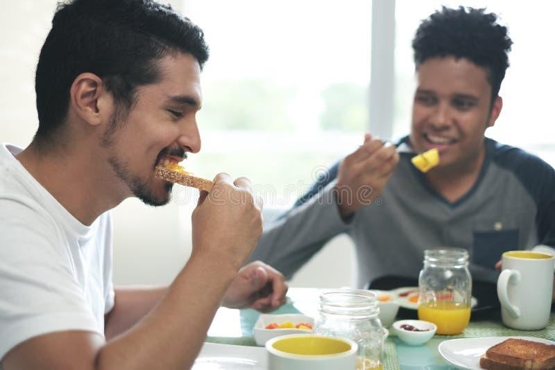 Glade par som hemma äter frukosten i morgonen royaltyfria bilder
