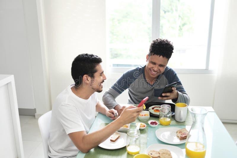 Glade par som hemma äter frukosten i morgonen royaltyfria foton