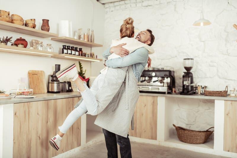 Glade par som kramar i mitt av k?ket fotografering för bildbyråer