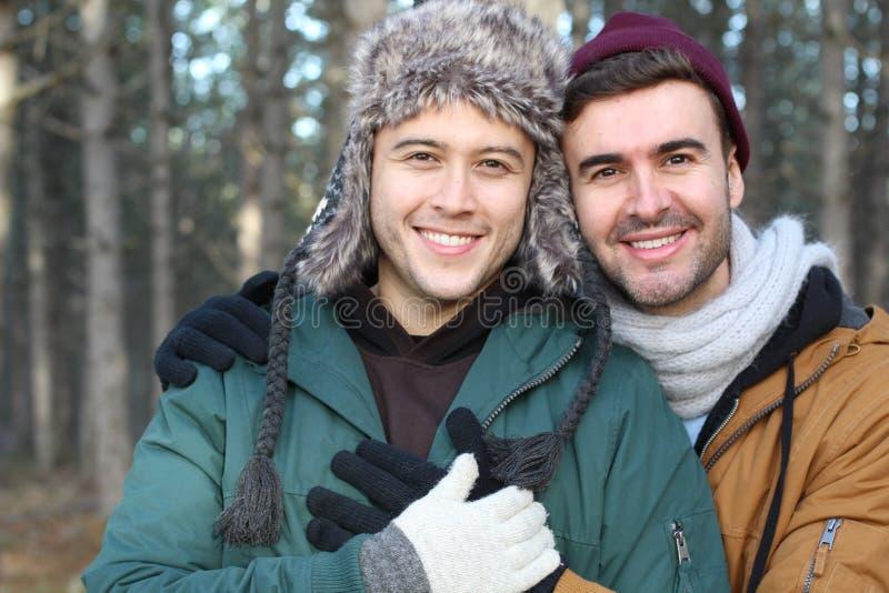 Glade par som ler i vintern royaltyfri foto