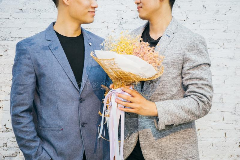 Glade par som rymmer en bukett av blommor, ordnar till för att ge sig till hans partner för speciala tillfällen eller gifta sigfö royaltyfri foto
