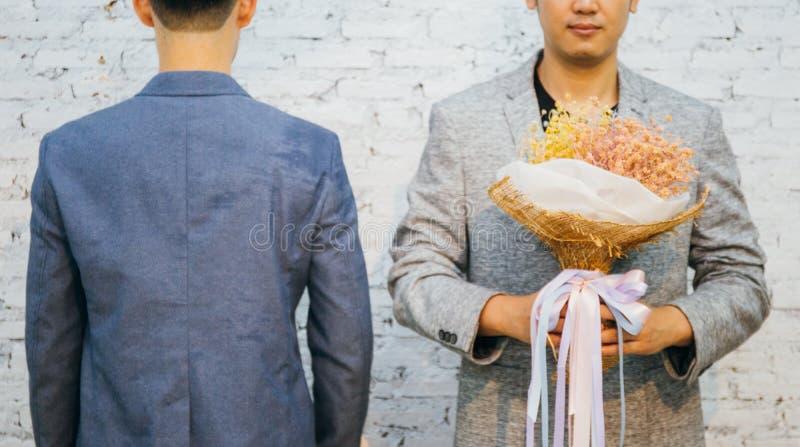 Glade par som rymmer en bukett av blommor, ordnar till för att ge sig till hans partner för speciala tillfällen eller gifta sigfö arkivbild
