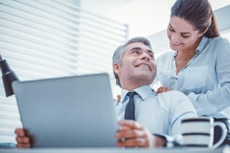 Glade partners som har ett romantiskt förhållande på arbete royaltyfria foton