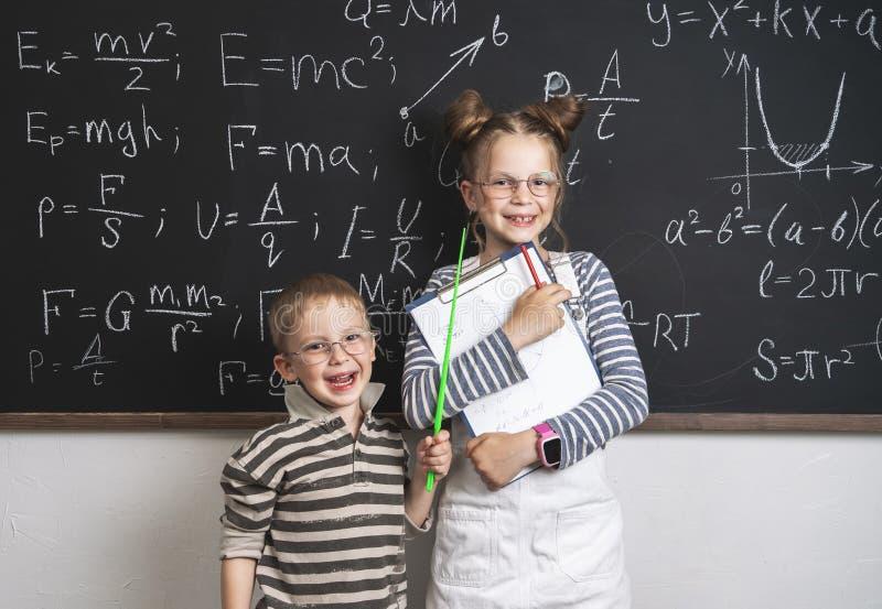 Glade pojke- och flickaelever står på svart tavla och stetradsna Många formler är skriftliga på svart tavla royaltyfria foton