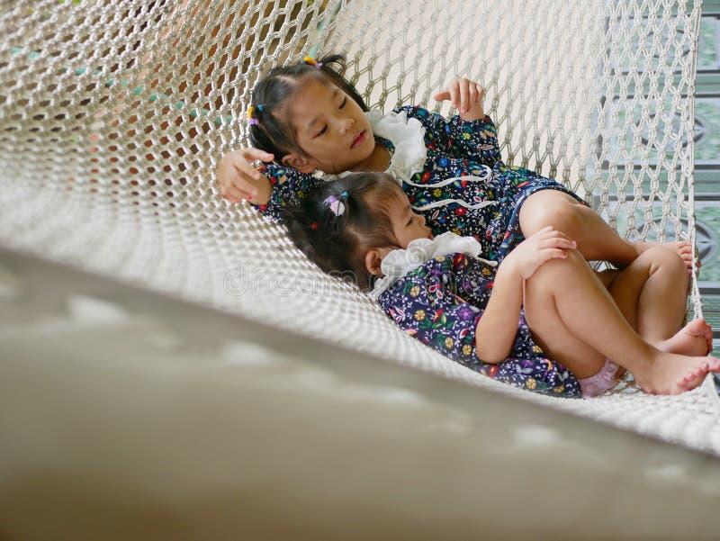 Glade små asiatiska flickor, systrar, gillar att vara tillsammans på en hammock - syskonförhållande arkivfoto