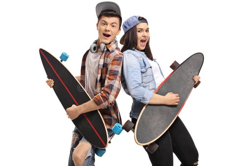 Glade tonåringar som låtsar för att spela gitarren på longboards royaltyfri foto