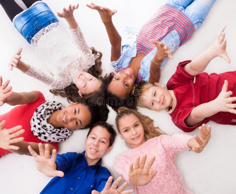 Glade tonåringar som ligger på golvhuvudet - - huvud royaltyfri bild