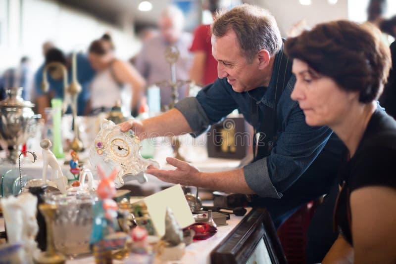 Glade turister studerar området av loppmarknaden arkivbilder