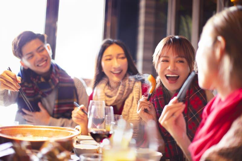 Glade unga vänner som äter en het pott på restaurangen royaltyfri foto