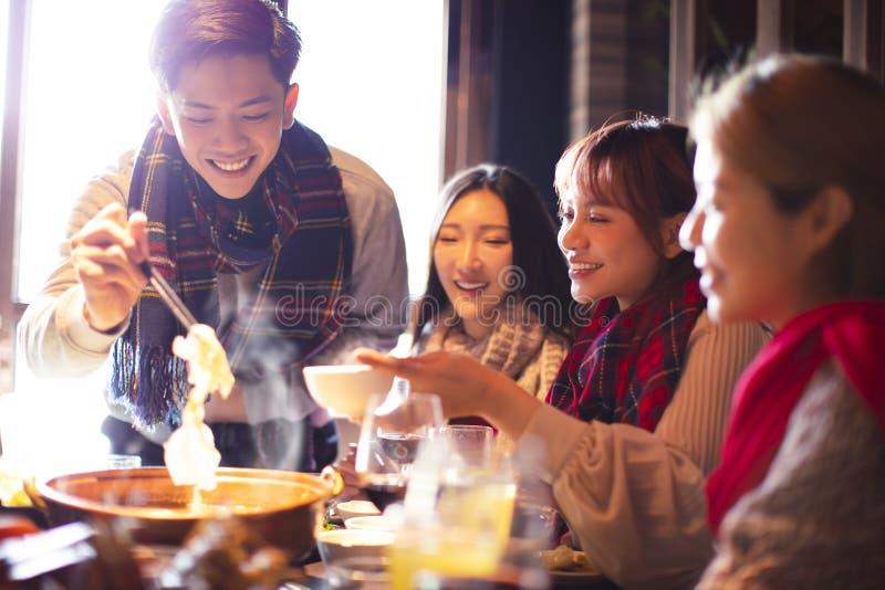 Glade unga vänner som äter en het pott på restaurangen arkivfoton