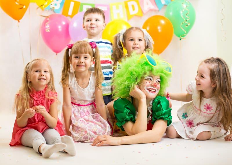 Glade ungar och clown på födelsedagpartiet royaltyfri fotografi