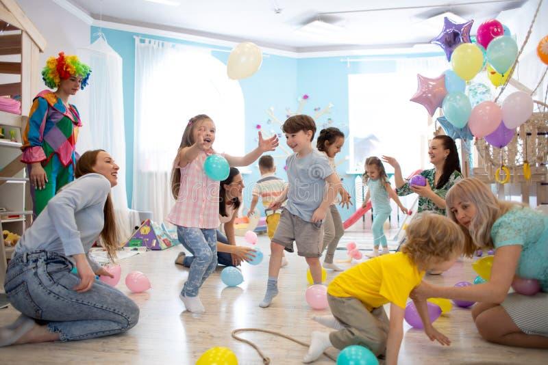 Glade ungar och deras föräldrar underhåller och har gyckel med färgballongen på födelsedagpartiet arkivbilder