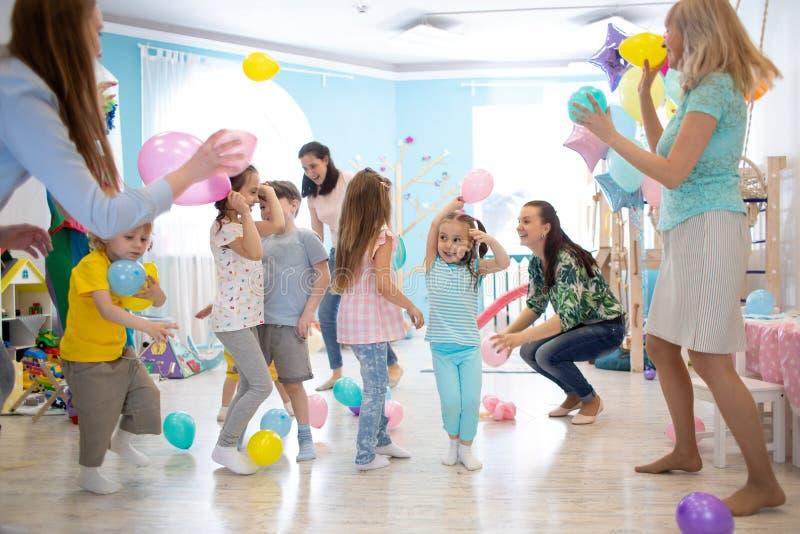 Glade ungar och deras f?r?ldrar underh?ller och har gyckel med f?rgballongen p? f?delsedagpartiet royaltyfri bild