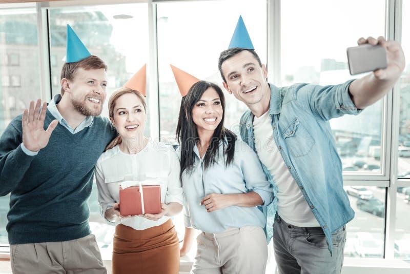 Glade vänliga kollegor som ler och gör fotoet royaltyfri foto