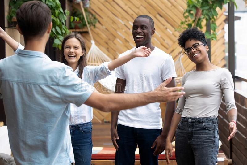 Glade vänner med flera raser känner sig entusiastiska när de träffar en vän i kaféet royaltyfri fotografi