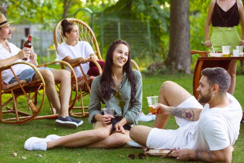 Glade vänner som äter och dricker öl vid barbemiddagen på solnedgången royaltyfria bilder