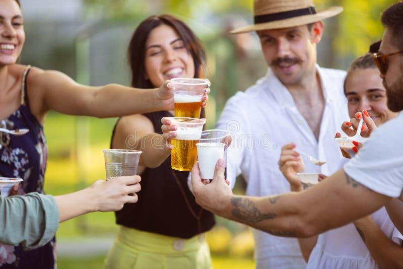Glade vänner som äter och dricker öl vid barbemiddagen på solnedgången arkivbilder