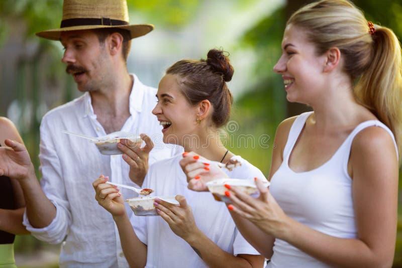 Glade vänner som äter pÃ¥ barbektmiddag pÃ¥ solnedgÃ¥ngen fotografering för bildbyråer