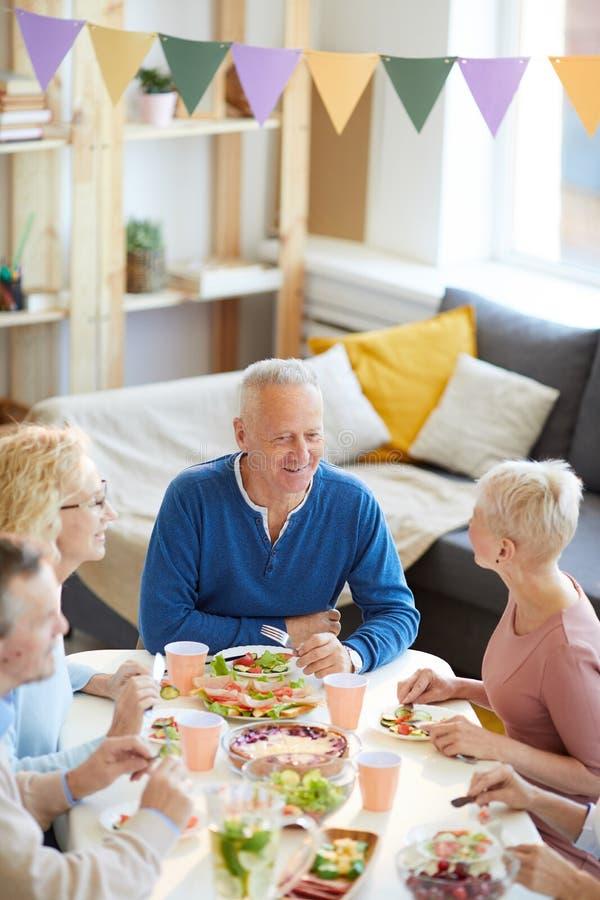 Glade vänner som tycker om kommunikation på matställepartiet royaltyfria foton