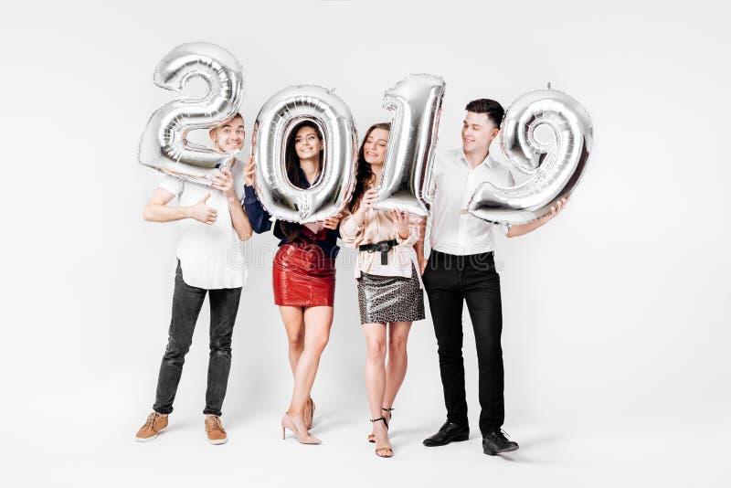 Glade vänner två flickor och två iklädda stilfulla kläder för grabbar rymmer ballonger i formen av nummer 2019 på a royaltyfri bild