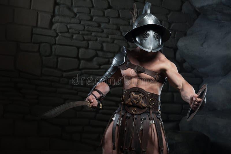 Gladiador en casco y armadura que sostiene la espada foto de archivo