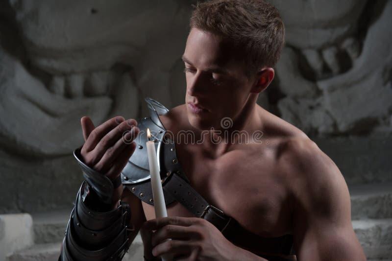 Gladiador en la armadura que se sienta en pasos de antiguo foto de archivo libre de regalías