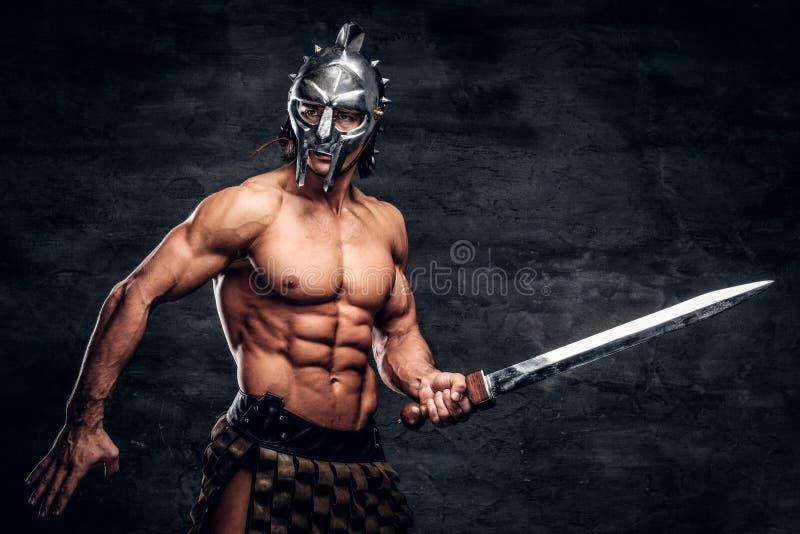 Gladiador fuerte con la espada en sus manos imagen de archivo