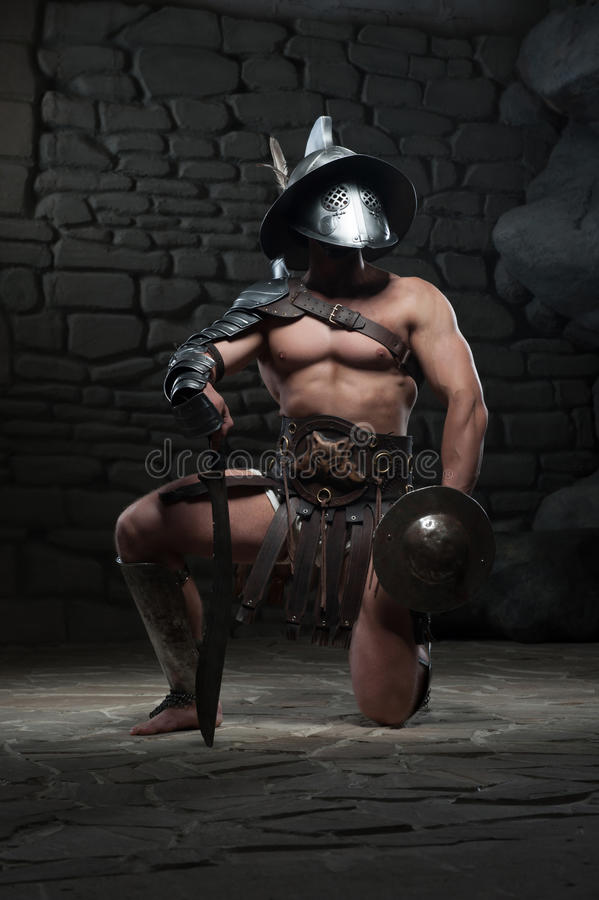 Gladiador no capacete e armadura que guarda a espada foto de stock royalty free