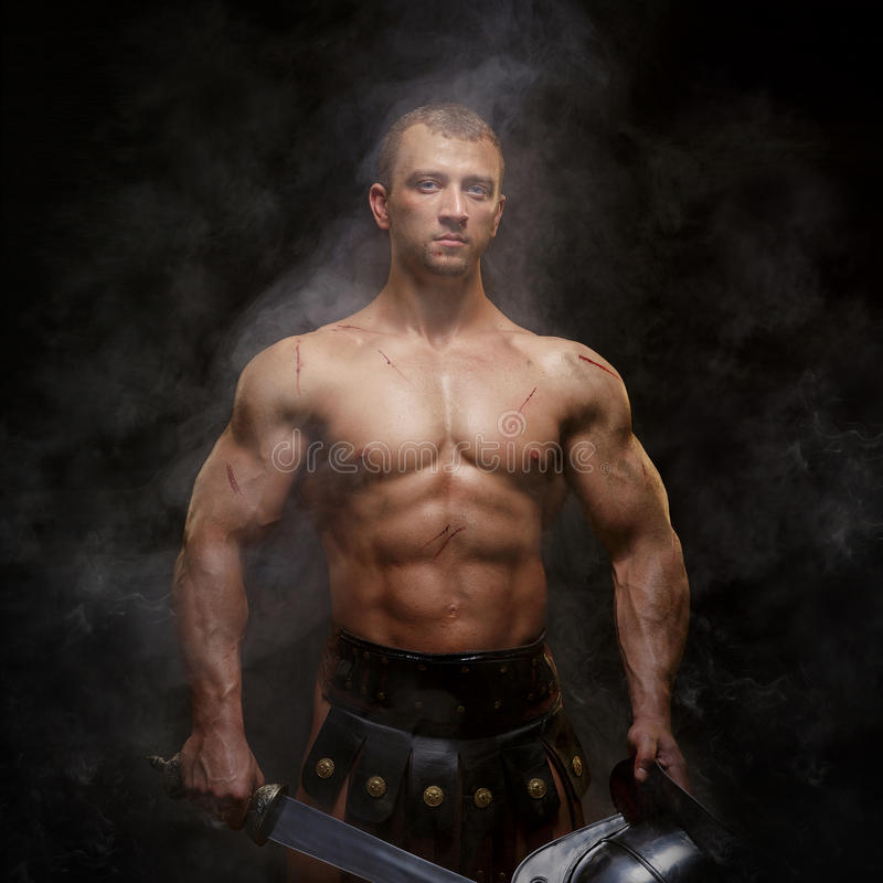 Gladiador que está em um fumo no capacete e com espada fotografia de stock royalty free