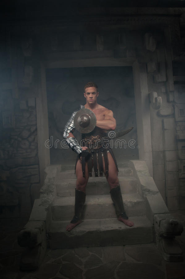 Gladiator in armour standing on steps of ancient stock photo