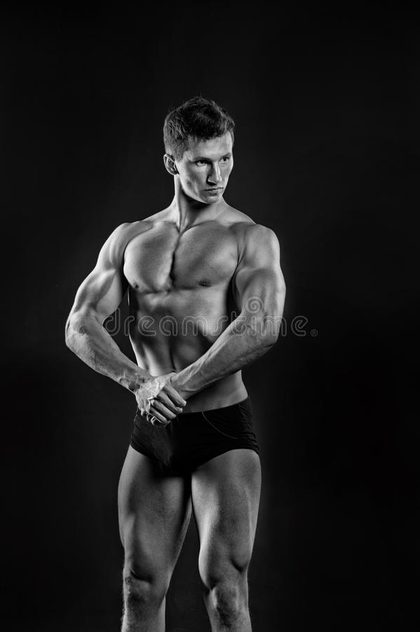 Gladiator or atlant. Adam with bare chest. Athletic bodybuilder pose in pants. Sport and workout. Man with muscular body, black and white royalty free stock photography