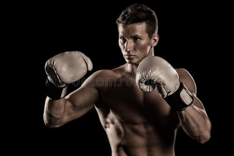 Gladiator or atlant in boxing gloves. Athletic bodybuilder pose in pants. Man with muscular body. Sport and workout. Boxer with bare chest royalty free stock photo