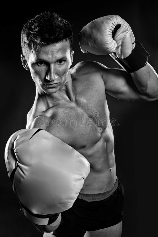 Gladiator or atlant in boxing gloves. Sport and workout. Boxer with bare chest. Man with muscular body. Athletic bodybuilder pose in pants, black and white stock photo