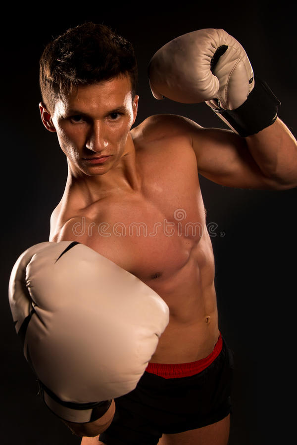 Gladiator or atlant in boxing gloves. Sport and workout. Man with muscular body. Boxer with bare chest. Athletic bodybuilder pose in pants stock photo