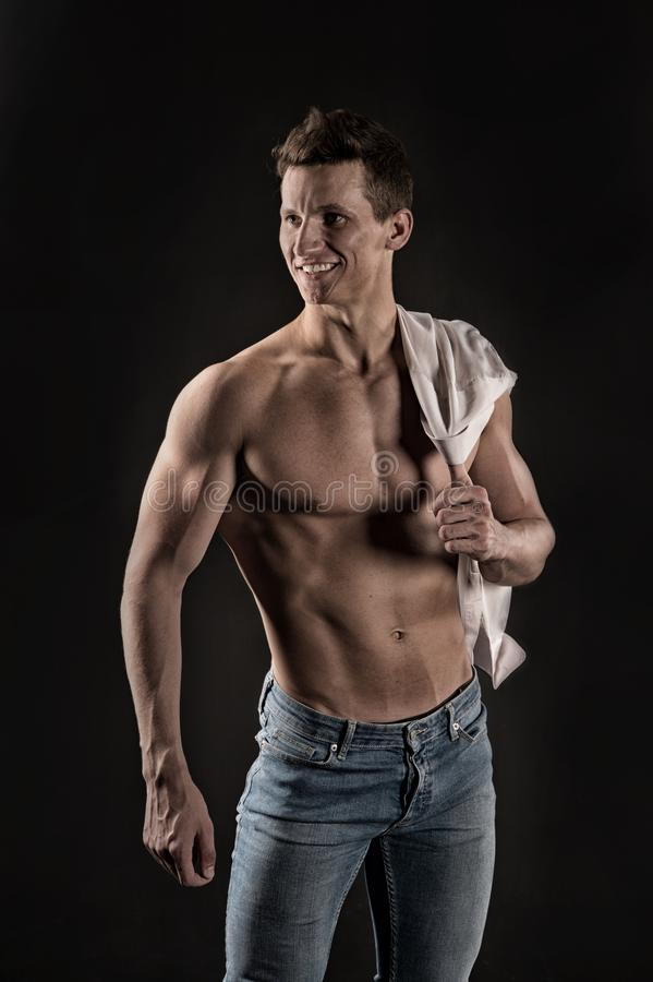 Gladiator or atlant. Guy with bare chest in jeans and shirt. Athletic bodybuilder pose. Sport and workout. Man with muscular body royalty free stock photo
