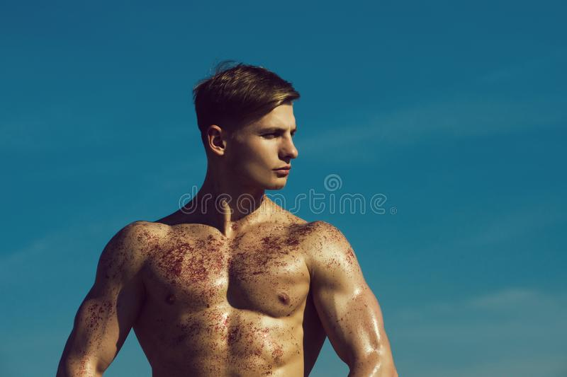 Gladiator or atlant. Man with muscular wet body. Adam with glitter on bare chest. Athletic bodybuilder pose as hercules. Sport and workout royalty free stock photography