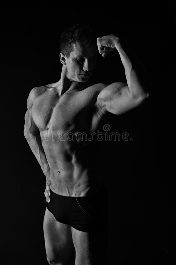 Gladiator or atlant. Sport and workout. Athletic bodybuilder pose in pants. Man with muscular body. Adam with bare chest, black and white stock image