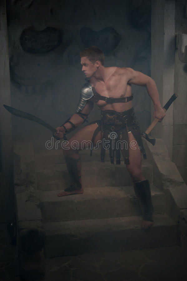 Gladiator in der Rüstung, die auf Schritten von altem steht stockfotografie
