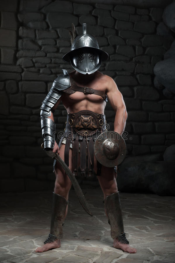 Gladiator in helmet and armour holding sword stock images