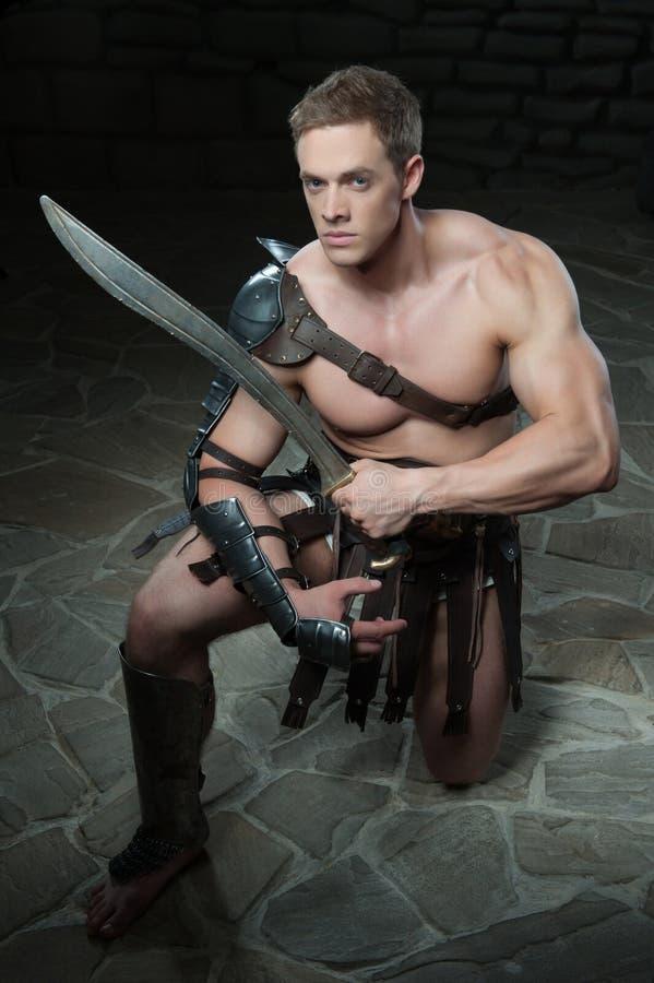 Gladiator met zwaard het knielen royalty-vrije stock foto's