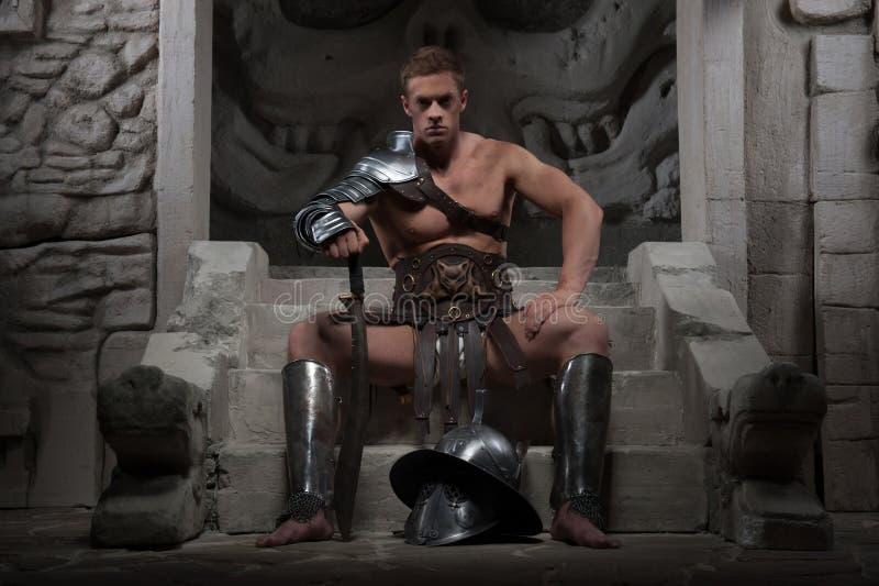 Gladiator w zbroi obsiadaniu na krokach antyczny obraz stock