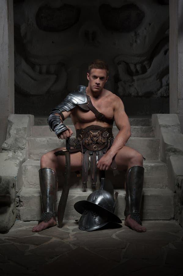 Gladiator w zbroi obsiadaniu na krokach antyczny obraz royalty free