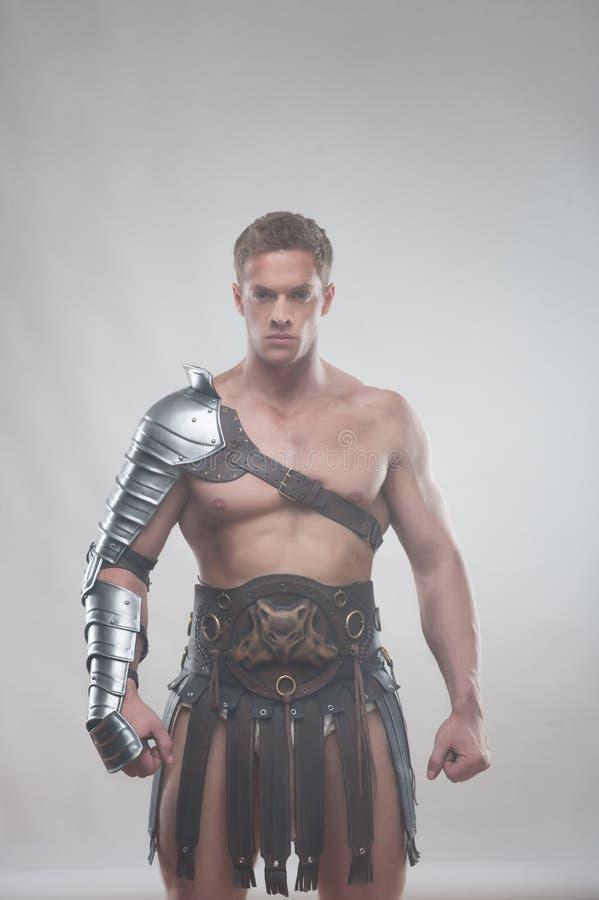 Gladiator w zbroi pozuje nad popielatym tłem obraz royalty free