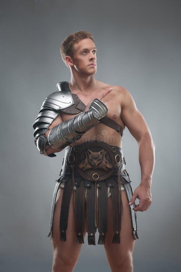 Gladiator w zbroi pozuje nad popielatym tłem fotografia royalty free