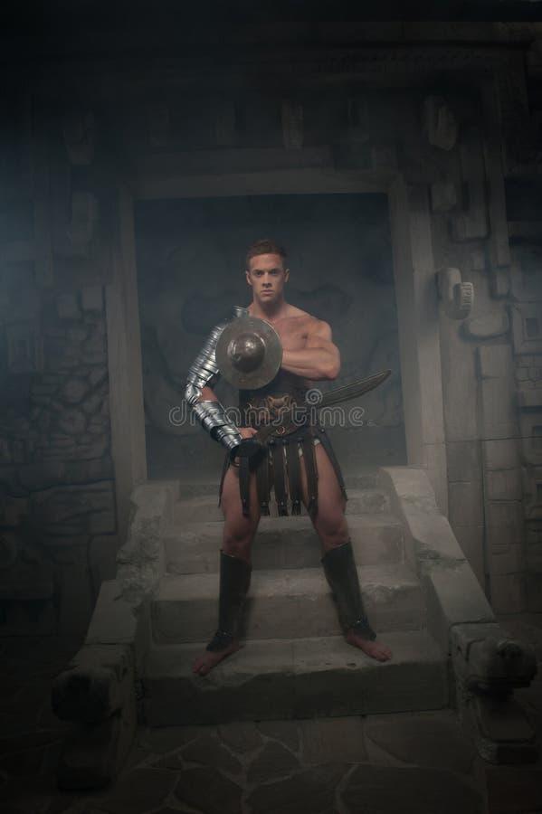 Gladiator w zbroi pozyci na krokach antyczny zdjęcie stock