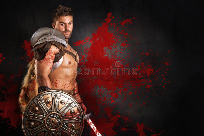 Gladiator/Warrior. Ancient warrior or Gladiator posing over a dark background royalty free stock photo